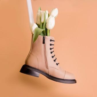 Wiosenne buty na brązowym tle. beżowe botki z białymi tulipanami