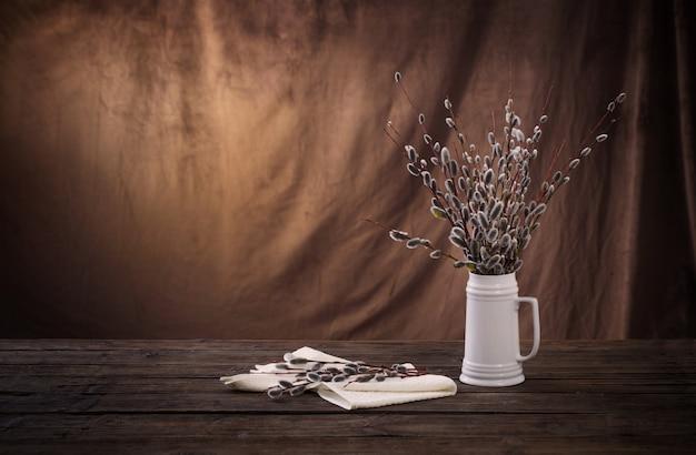 Wiosenne gałązki wierzby w białym dzbanku na brązowym ciemnym tle