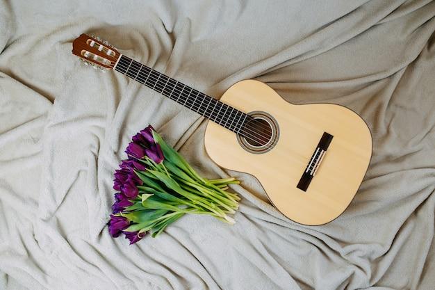 Wiosenne kwiaty, fioletowe tulipany, biała gitara i kwiaty na szarym tle, plakat muzyczny wiosna.