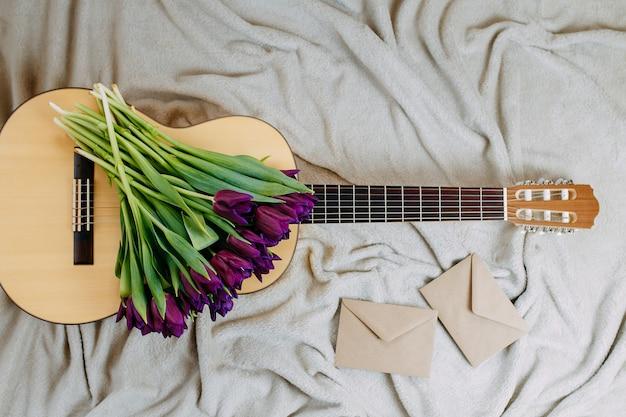 Wiosenne kwiaty, fioletowe tulipany, biała gitara i kwiaty na szarym tle, wiosenny plakat muzyczny, bukiet fioletowych tulipanów na gitarze, koperty z papieru rzemieślniczego.