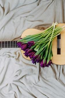 Wiosenne kwiaty, fioletowe tulipany, biała gitara i kwiaty na szarym tle, wiosenny plakat muzyczny, bukiet fioletowych tulipanów na gitarze.