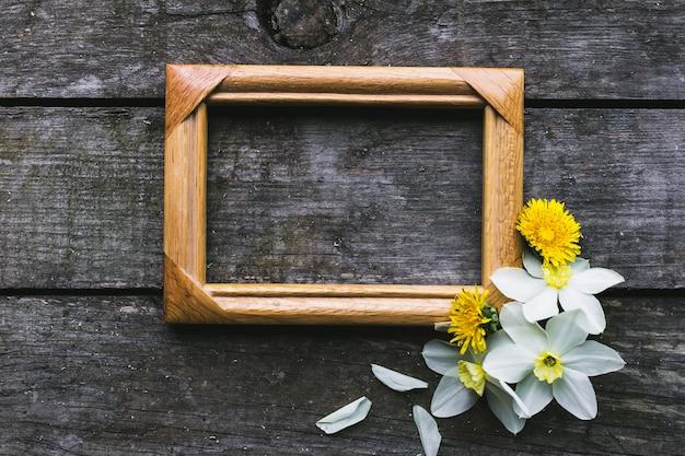 Wiosenne kwiaty i rama na starym drewnianym tle