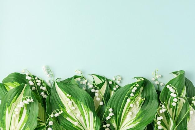 Wiosenne kwiaty konwalii na pastelowo niebieskiej powierzchni