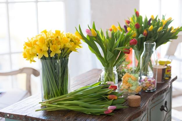 Wiosenne kwiaty na drewnianym stole. w pomieszczeniach naturalne światło przy niewielkiej głębi ostrości