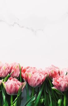 Wiosenne kwiaty na marmurowym tle jako karta z pozdrowieniami świątecznymi i kwiatowy koncepcja flatlay