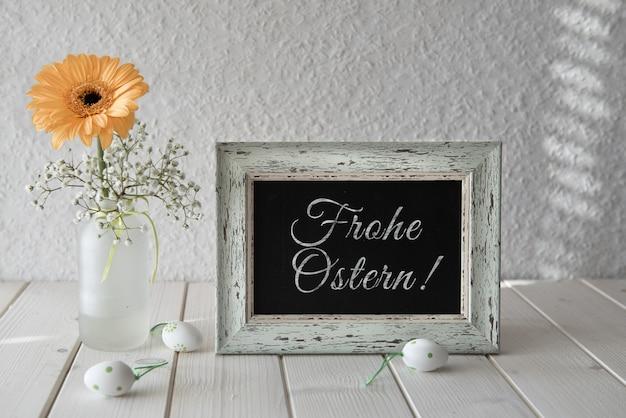 Wiosenne kwiaty, ozdoby wielkanocne i tablica na białym stole, tekst