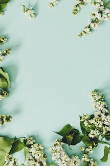 Wiosenne kwiaty. rama z gałązek kwitnących bzu biały na niebieskim tle. widok z góry. miejsce na tekst