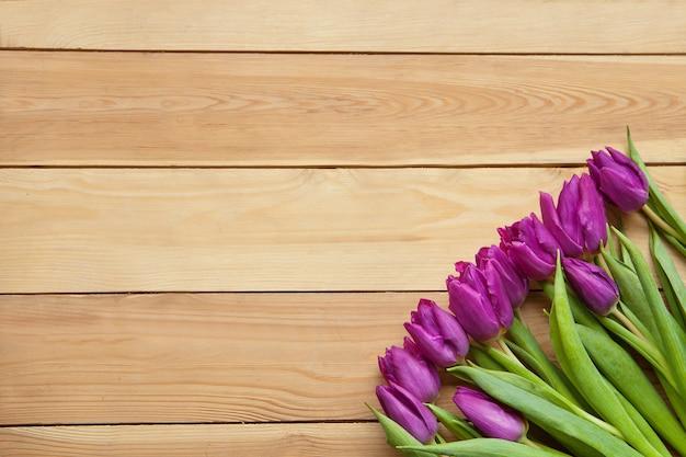 Wiosenne kwiaty tulipanów na drewnianym stole fioletowe piękne tulipany z zielonymi liśćmi na pocztówkę