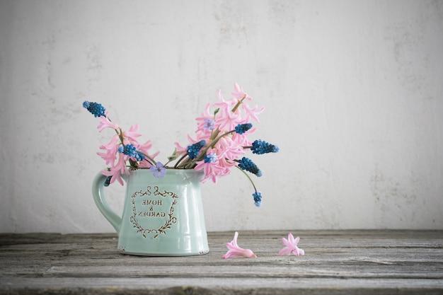 Wiosenne kwiaty w niebieskim dzbanku na stole grunge