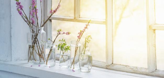 Wiosenne kwiaty w słoikach na starym białym parapecie