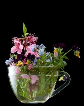 Wiosenne kwiaty w szklanym pojemniku z czarnym na białym tle