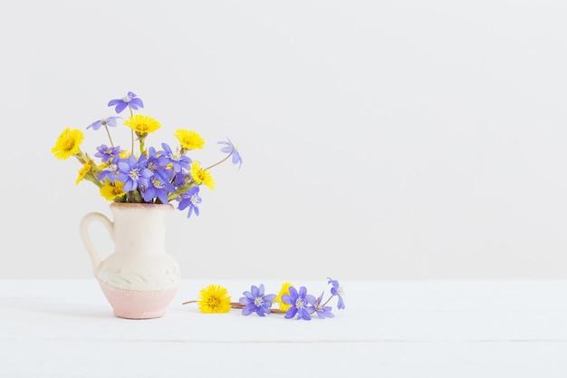 Wiosenne kwiaty w wazonie na białej powierzchni