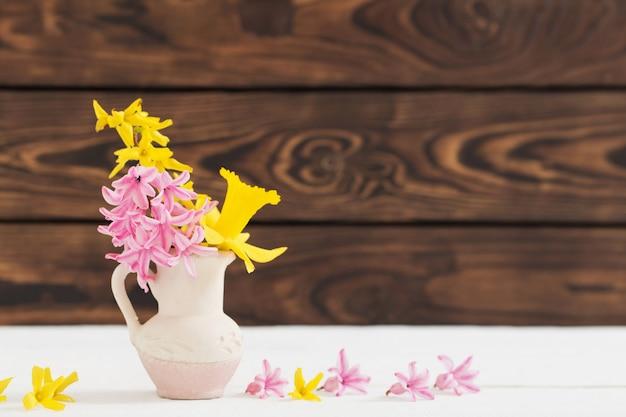 Wiosenne kwiaty w wazonie na drewnianym