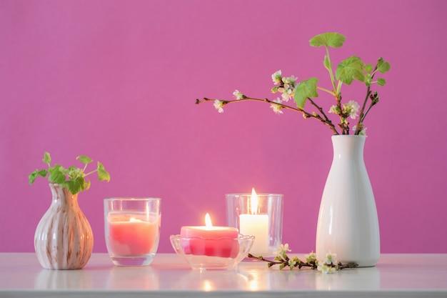 Wiosenne kwiaty wiśni i świece na różowym tle