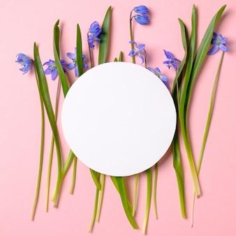 Wiosenne kwiaty z niebieskimi płatkami i puste karty papieru w kształcie koła zębatego na pastelowym różowym tle.