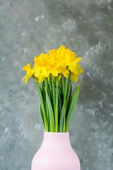 Wiosenne kwiaty, żółte żonkile w wazonie na szarym tle.