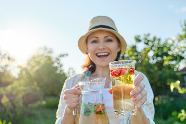 Wiosenne letnie napoje, kobieta w naturze trzymająca słoik truskawkowej mięty i cytryny