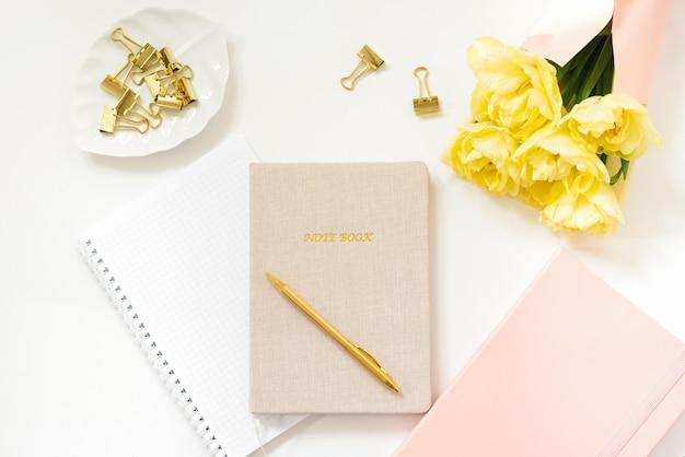 Wiosenne mieszkanie leżało w różowo-żółtych kolorach dla samozatrudnionej niezależnej dziewczyny. praca w domu. zeszyty i pamiętniki, długopis, bukiet tulipanów