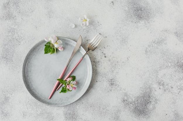 Wiosenne nakrycie stołu z kwitnącymi gałęziami jabłoni i kwiatami na lekkim stole