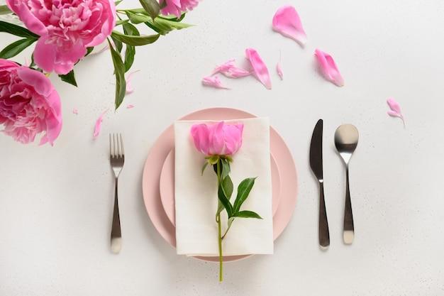 Wiosenne nakrycie stołu z różowymi kwiatami piwonii na białym stole. widok z góry.