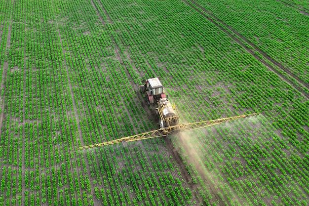 Wiosenne prace rolnicze na polach. ciągnik opryskuje uprawy herbicydami, insektycydami i pestycydami.