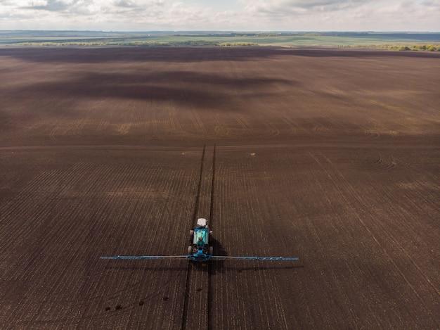 Wiosenne prace rolnicze na polach ciągnik spryskuje uprawy herbicydami, insektycydami i pestycydami