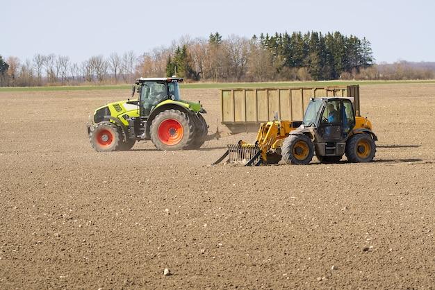 Wiosenne prace u rolnika w ciągniku przygotowujące pole do siewu ziemi rolniczej i traktora