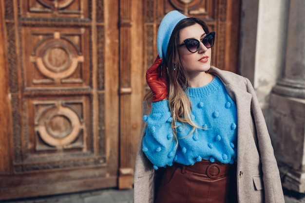Wiosenne retro moda retro kobiece akcesoria i ubrania. kobieta nosi sweter beret skórzaną spódnicę