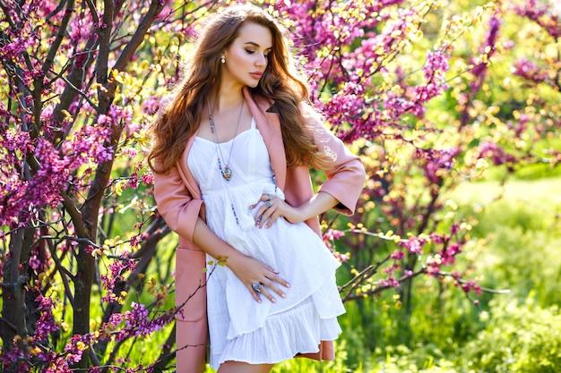 Wiosenne trendy portret eleganckiej wspaniałej pięknej stylowej kobiety pozującej w pobliżu kwitnących drzew w miejskim ogrodzie