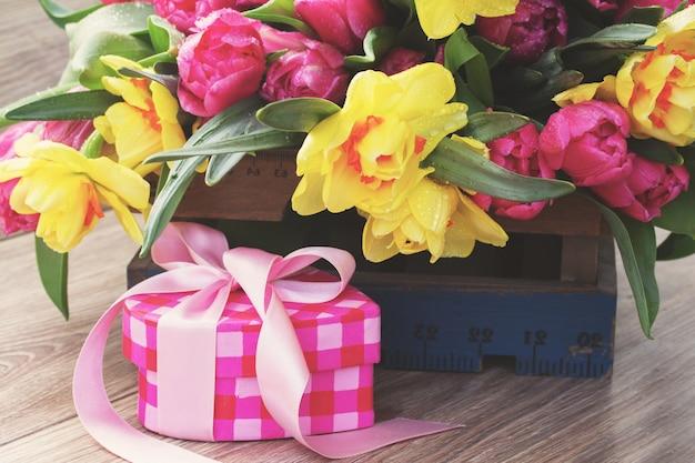 Wiosenne tulipany i żonkile z różowym pudełkiem na prezent z filtrem retro instagram