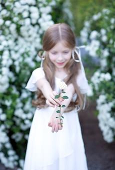 Wiosenny biały kwiat przedstawiający blondynkę z długimi włosami w białej sukni