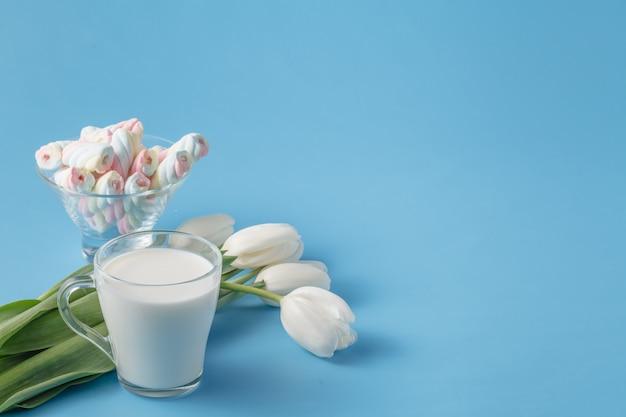 Wiosenny bukiet białych tulipanów, pianek i kubek mleka