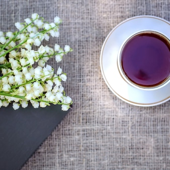 Wiosenny bukiet konwalii na książce i filiżankę herbaty