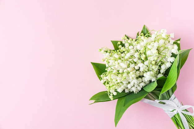 Wiosenny bukiet kwiatów konwalii na pastelowym różu