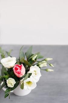 Wiosenny bukiet w białym wazonie na drewnianym białym stojaku. róże, tulipany i lisianthus.