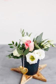 Wiosenny bukiet w przezroczystym szklanym wazonie na drewnianej gwieździe. róże, tulipany i lisianthus.