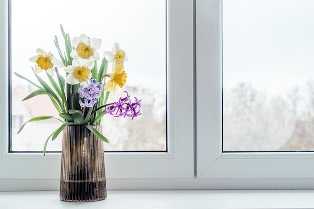 Wiosenny bukiet żółtych narcyzów i niebiesko-fioletowego hiacyntu w szklanym wazonie na parapecie