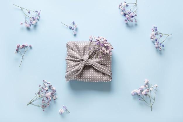 Wiosenny ekologiczny prezent zapakowany w szary materiał w niebieskie kwiaty.