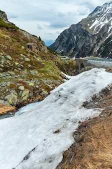 Wiosenny krajobraz górski alp z alpejską drogą i małym strumieniem (przełęcz fluela, szwajcaria)