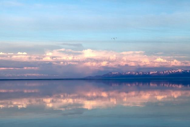 Wiosenny krajobraz z jeziorem i pięknymi refleksami, w delikatnych kolorach, tuż przed zachodem słońca