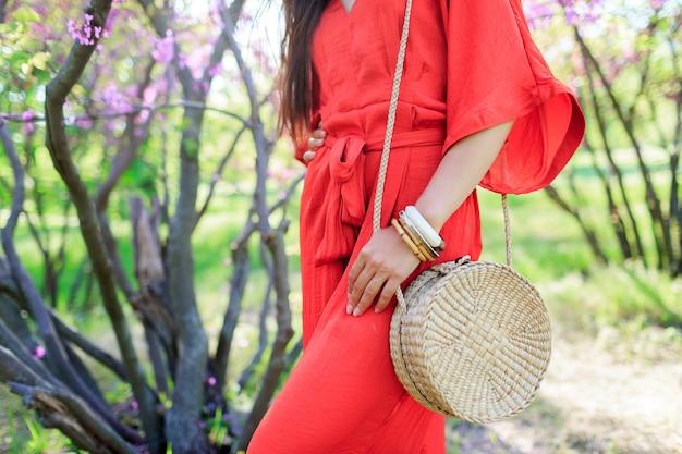 Wiosenny modny wygląd, kobieta trzymająca stylową, modną czeską torebkę ze słomy z rattanu bali i ubrana w koralową sukienkę boho.