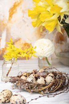 Wiosenny nastrój: martwa natura z gniazdem, jaja przepiórcze, kwiaty
