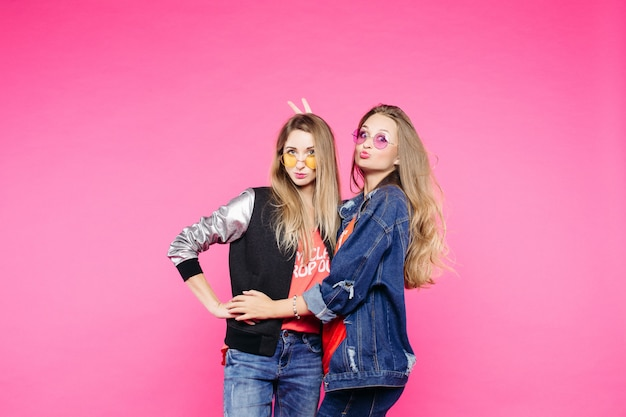 Wiosenny obraz dwóch pozytywnych dziewczyn w okularach, dziewczyn o prostych włosach, które się przytulają,