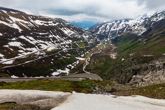 Wiosenny pochmurny krajobraz górski z serpentynami na przełęczy furka, szwajcaria