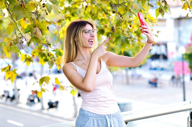 Wiosenny portret pięknej blondynki robiącej selfie i rozmawiającej na czacie wideo z przyjaciółką, swobodne sportowe ciuchy, słoneczne pastelowe kolory.