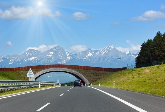 Wiosenny słoneczny widok na tatry wysokie ze śniegiem na zboczu góry i autostradzie (słowacja)