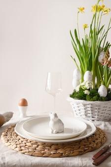 Wiosenny stylowy stół wielkanocny z ekologicznymi jajkami, zajączkiem i kwitnącymi kwiatami.