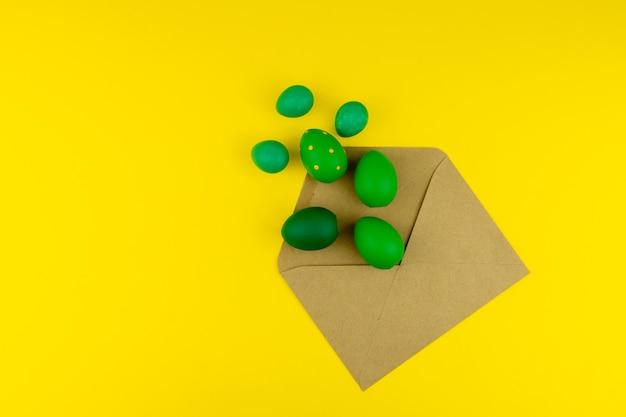 Wiosenny układ wielkanocny z zielonymi piórami i jajkami, koperta rzemieślnicza na żółtym tle. skopiuj miejsce na tekst na tekst.
