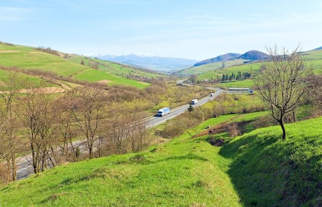 Wiosenny widok na dolinę górską z polami uprawnymi i drogą
