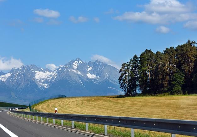 Wiosenny widok na wysokie tatry ze śniegiem na zboczu góry i autostradzie (słowacja)
